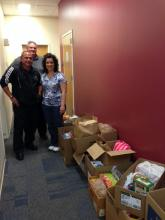Glenn Strause, Bob Bruneio and Carla Kologie (l-r) drop off the donations at Broughal Middle School